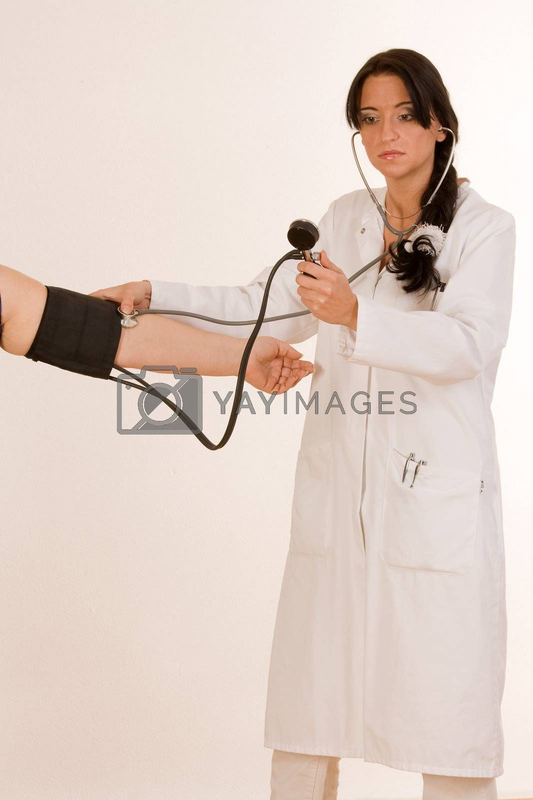 Physician measures the blood pressure at the arm of a patient
