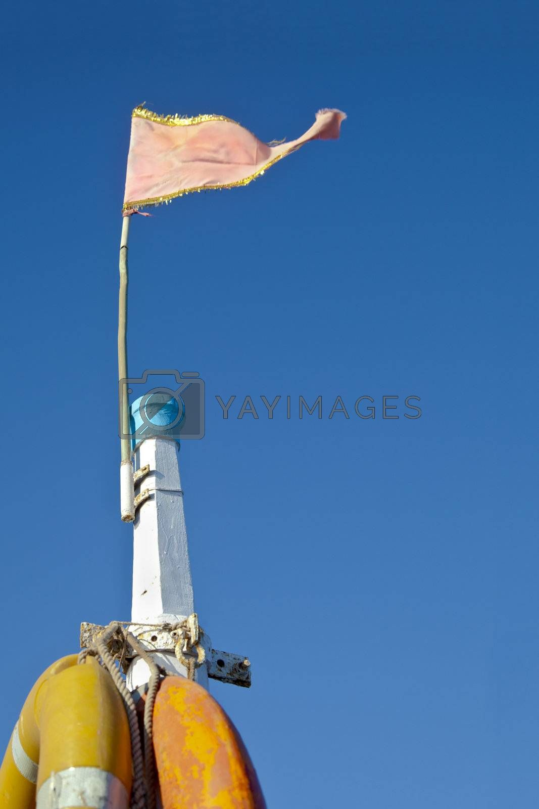 Dwarka Roadtrip. Concept of Rich blue sky split by a white mast bearing yellow life buoys and a pink frayed flag. Generic shot location Bet Dwarka, Gujarat, India