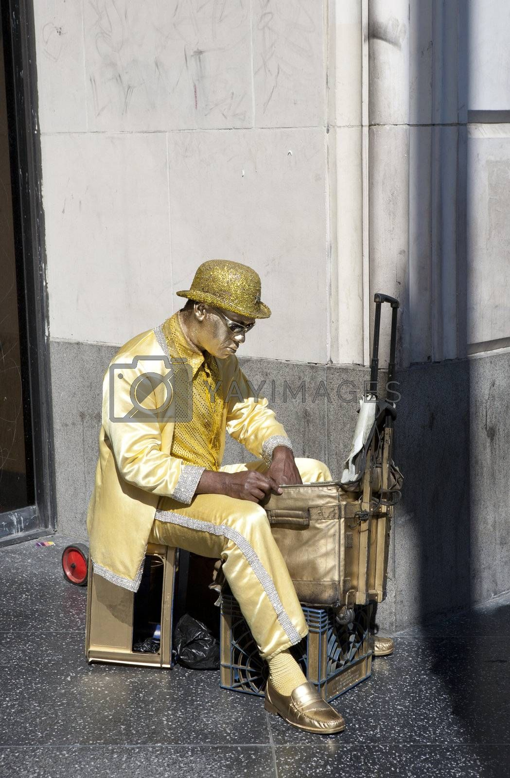 Street performer covered in gold paint getting ready to perform on a sidewalk on Hollywood Blvd.