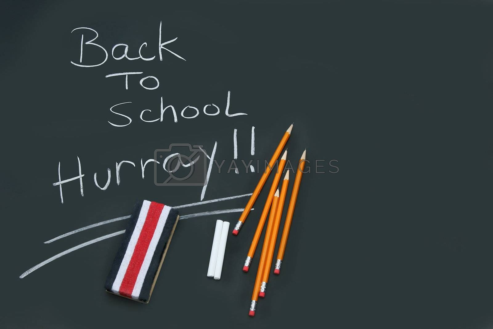 Back to school written on black chalkboard with pencils and eraser