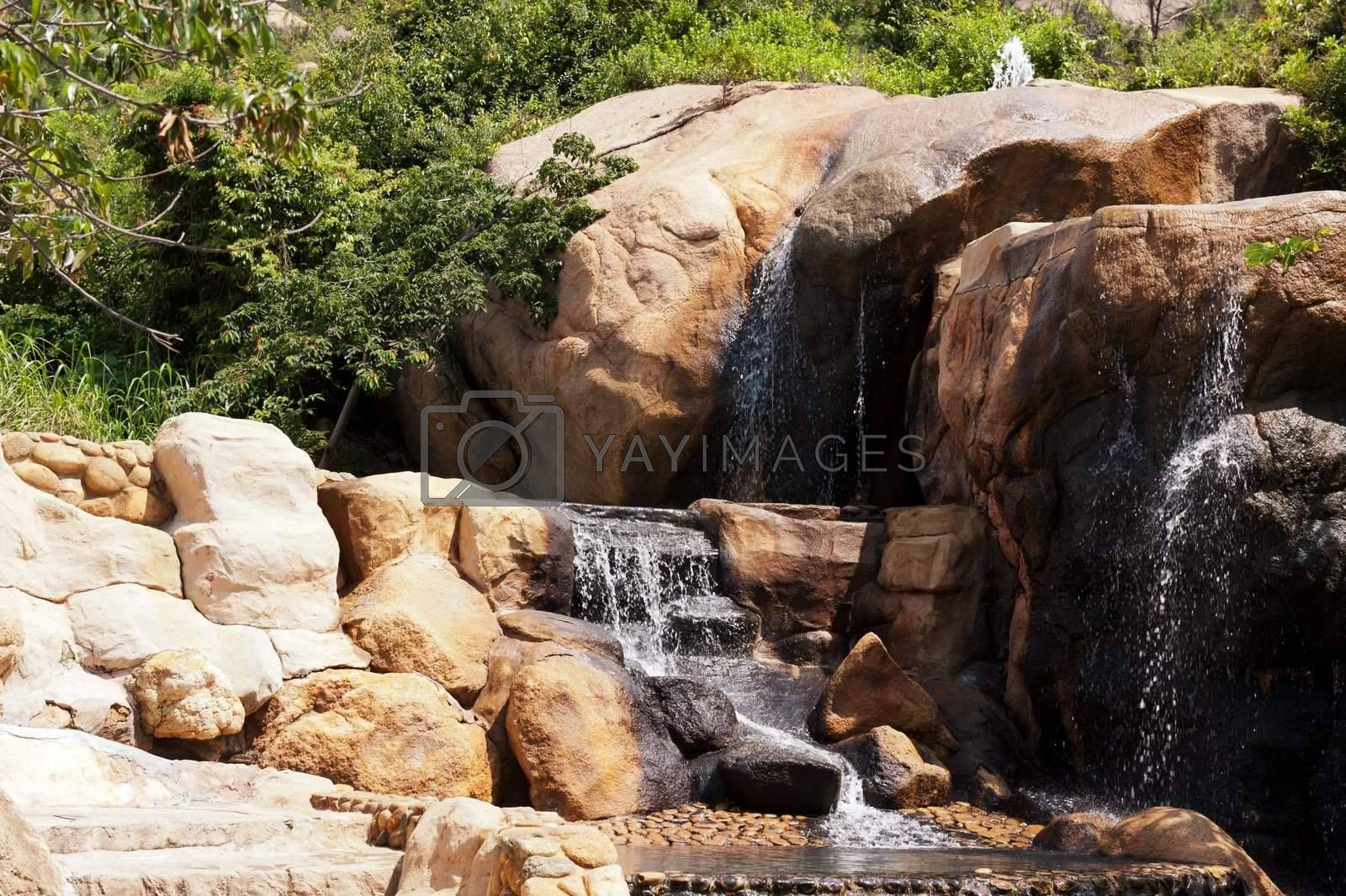 Waterfall in the garden with stones and trees