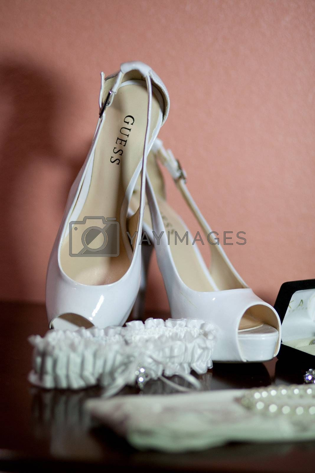 Bride's wedding shoes and other details against a wall