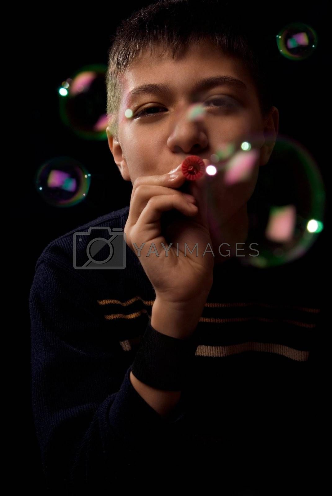 Photo of the young boy blowing soap bubbles