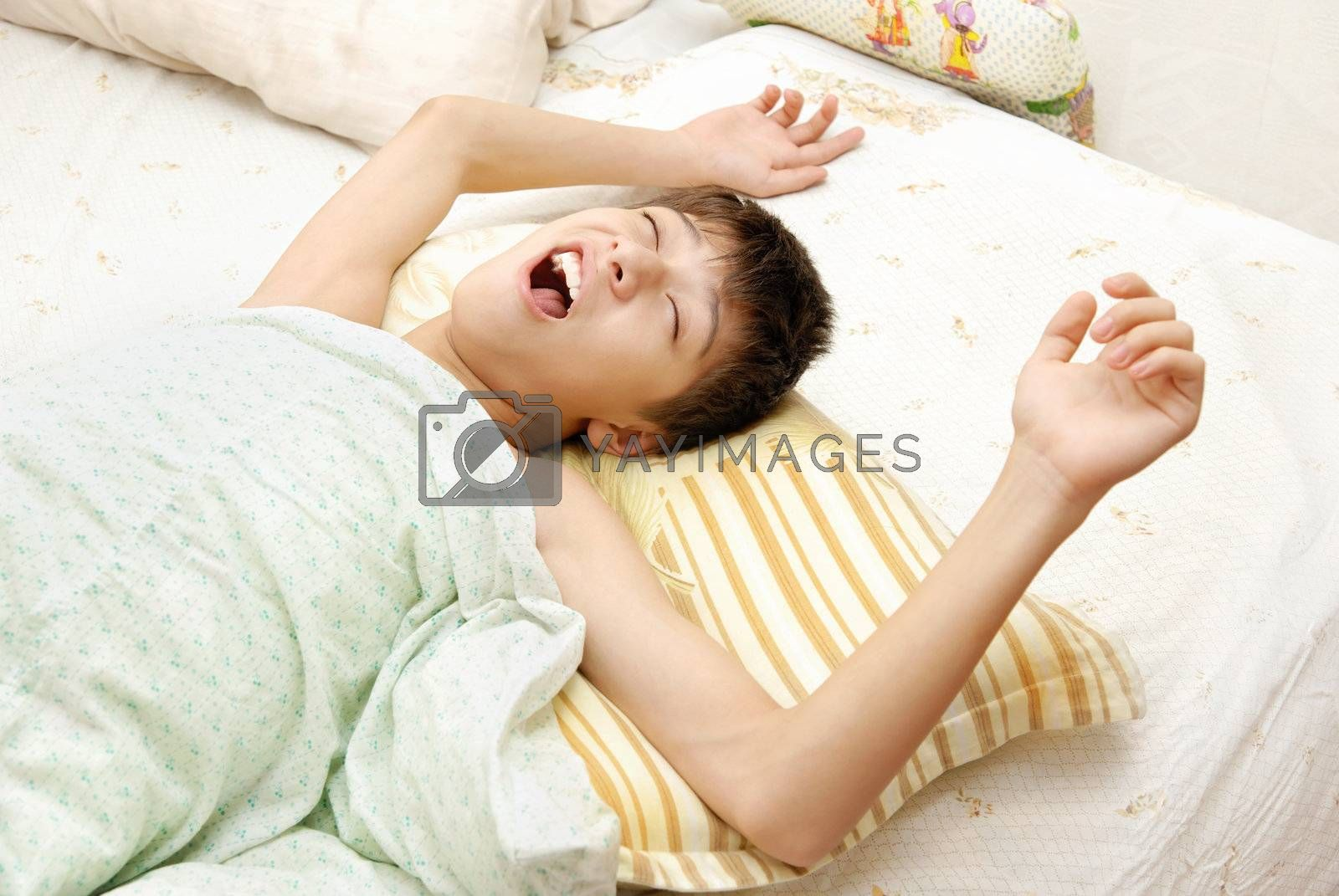 Yawning awaking boy on the bed at the early morning