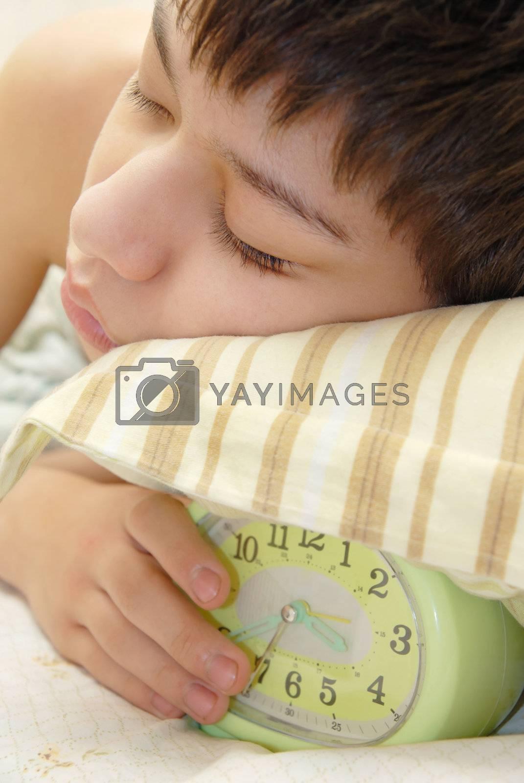 Deep sleeping boy and alarm-clock