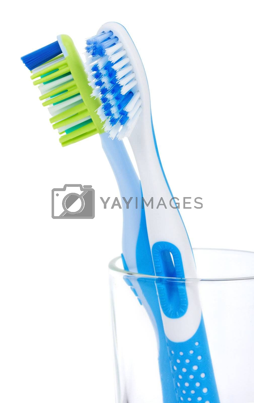 close-up two tooth brushes in glass, isolated on white