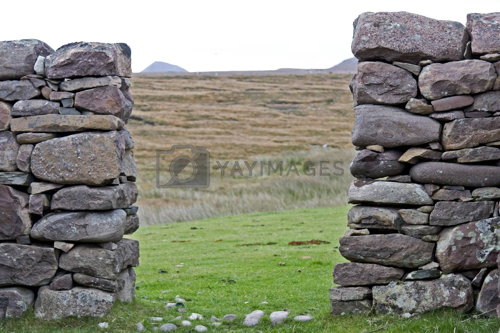 passage through stone wall with grazing land in background