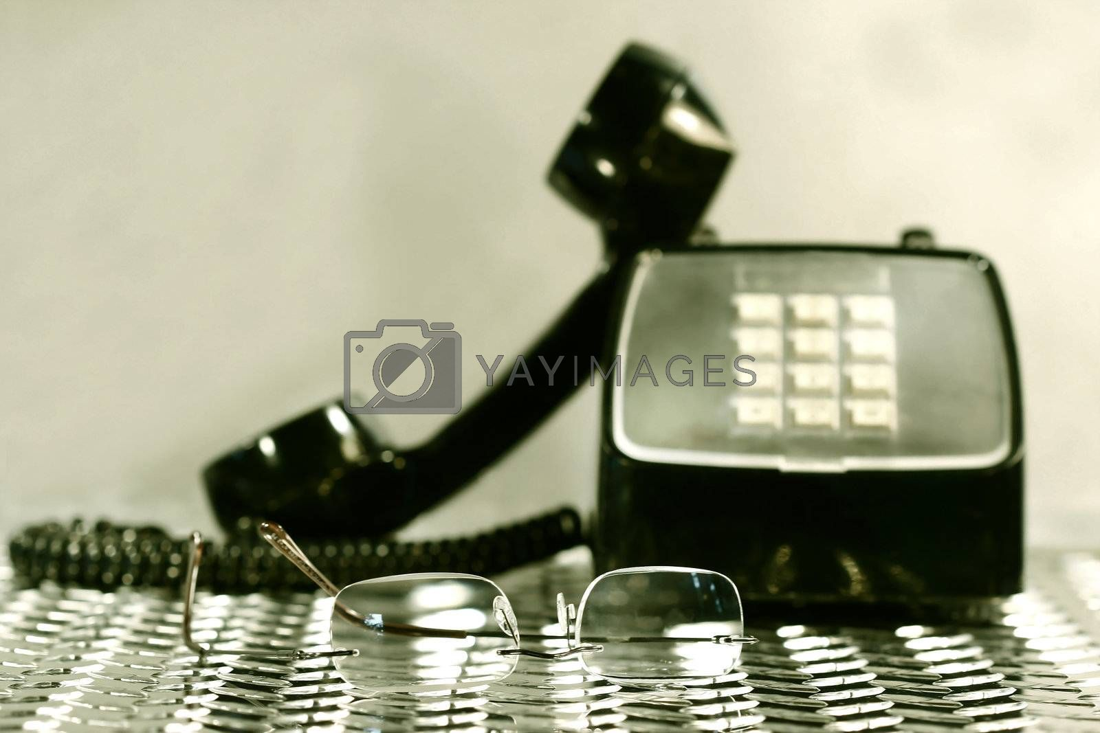 Black vintage telephone with a pair of reading glasses