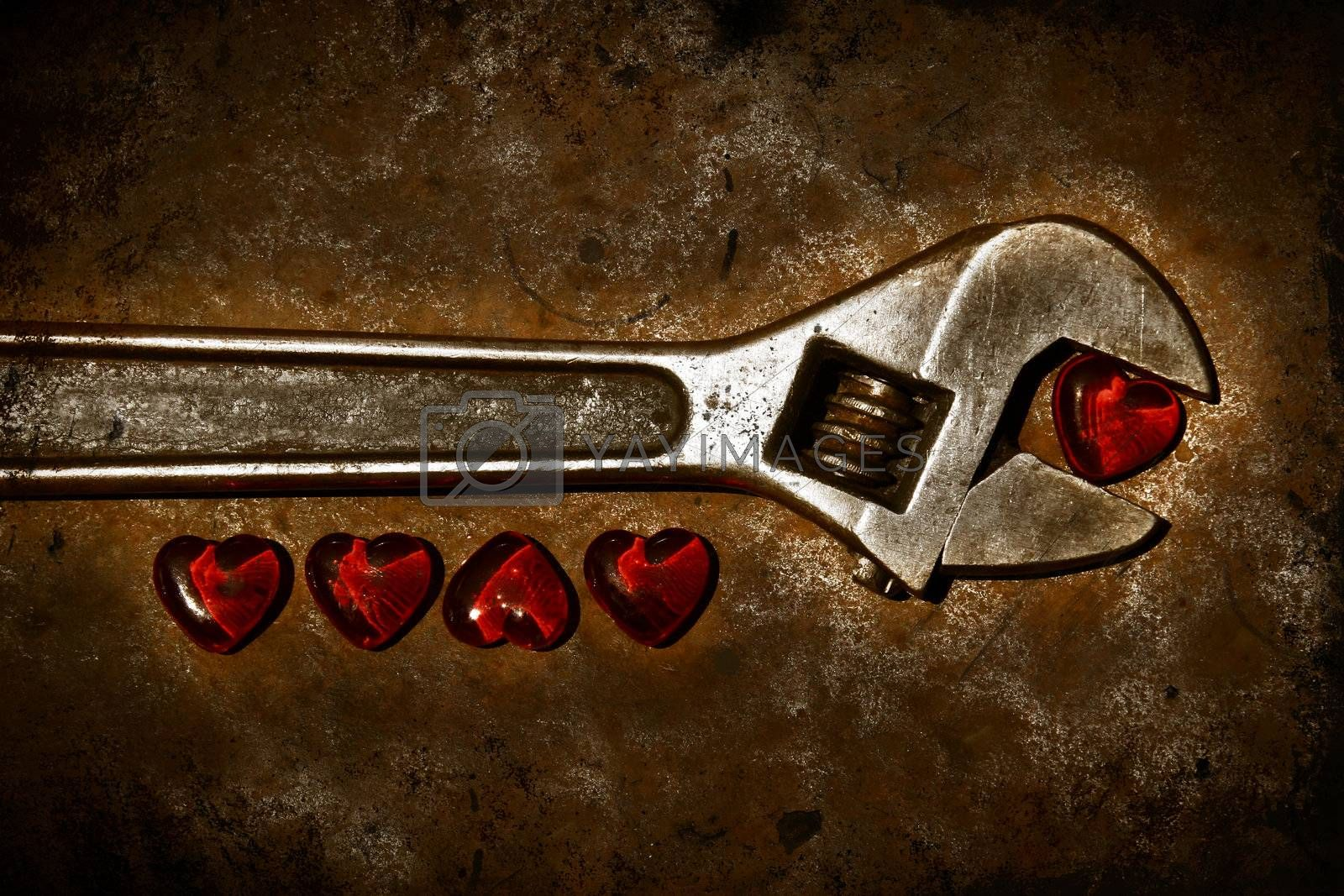 Five grunge hearts with wrench on rusty background