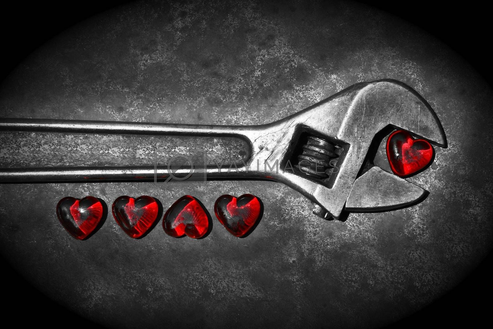 Five grunge hearts with wrench on rusty background/ BW
