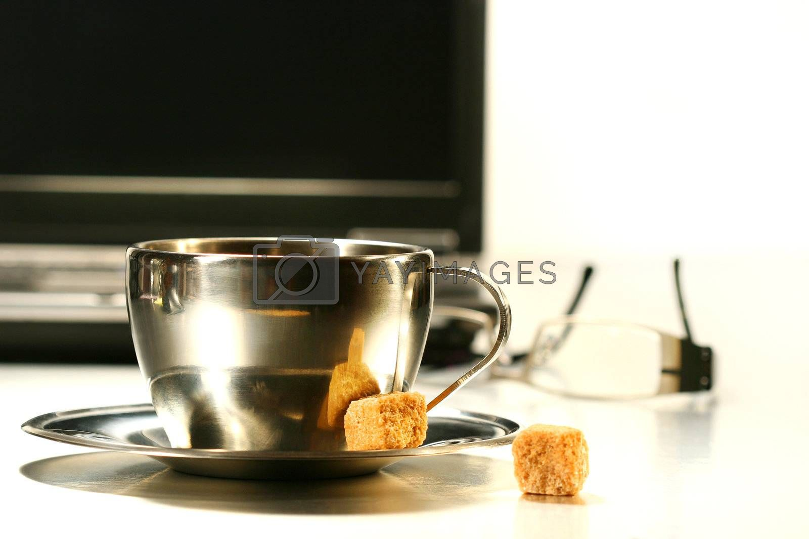 Stainless steel coffee cup with laptop in background
