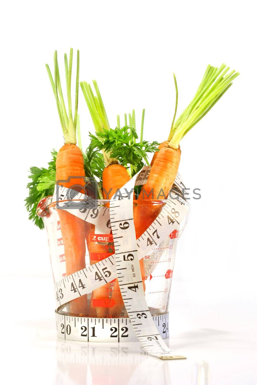 Carrots in a measuring cup with tape measure on white background
