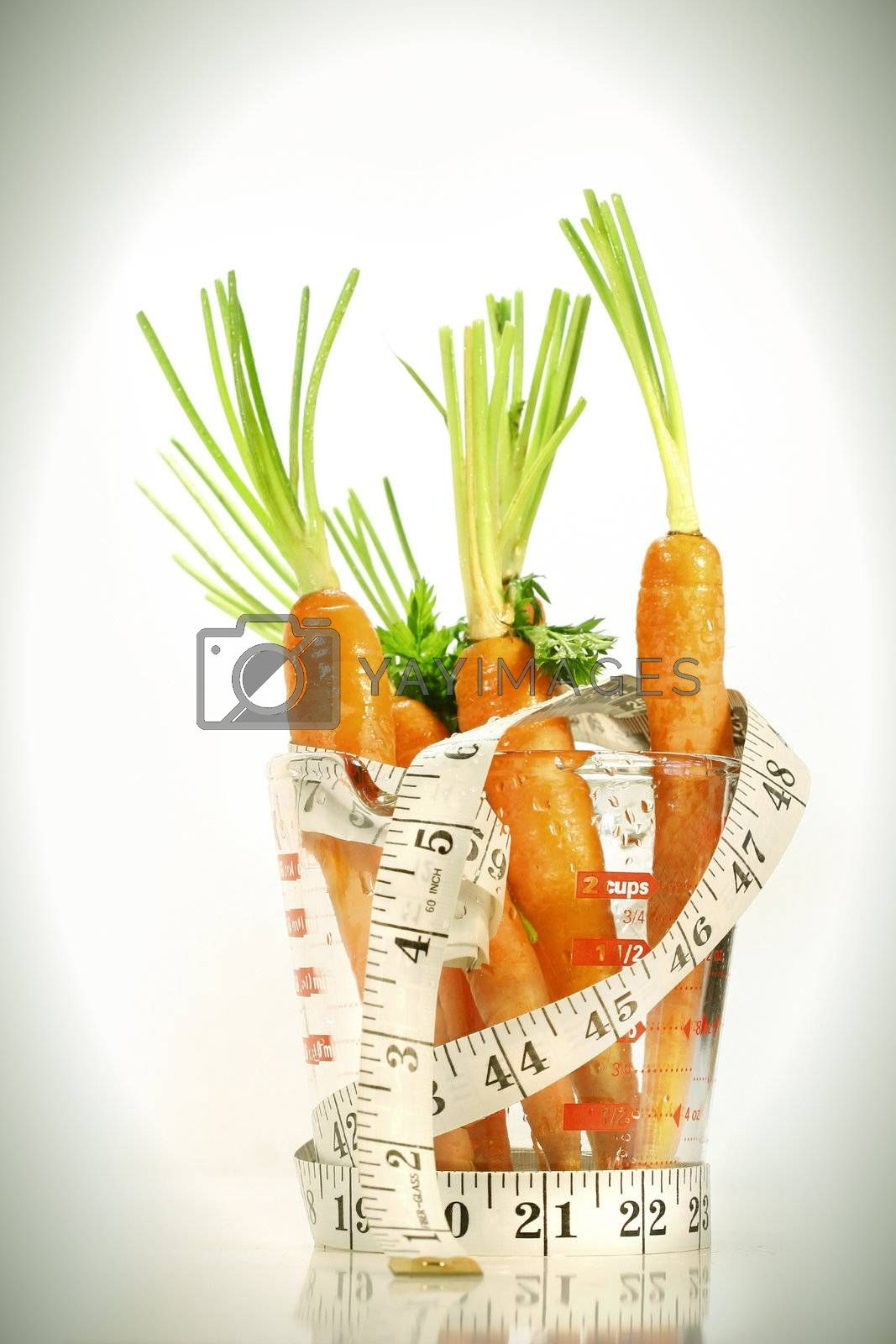 Carrots with water drops and a measuring tape wrapped around container