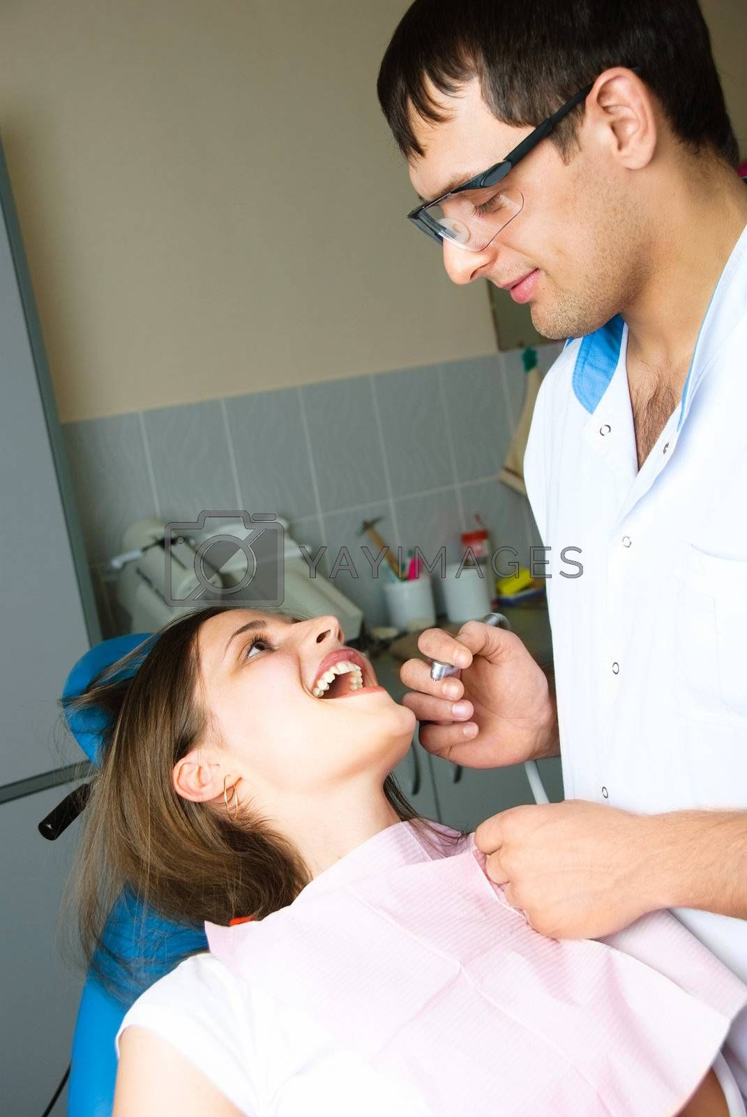 portrait of a young dentist examining the patient in his office