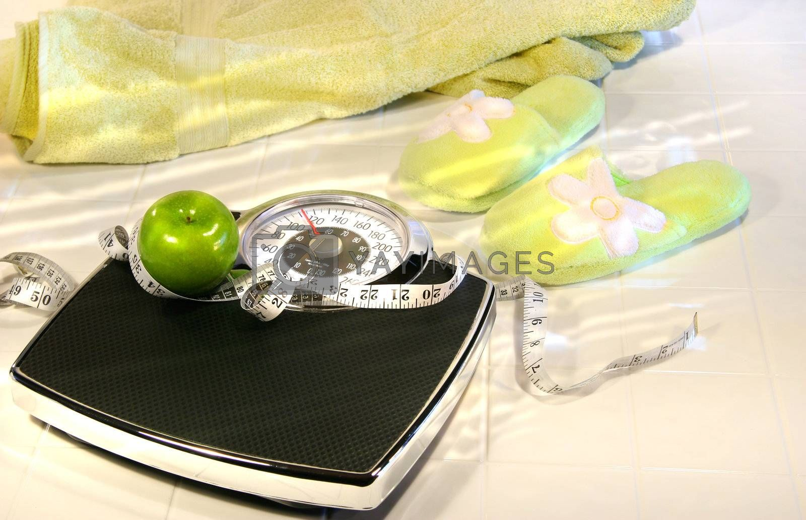 Weight scale on tile floor with towel and slippers/ Conceptual image for diet and excerise