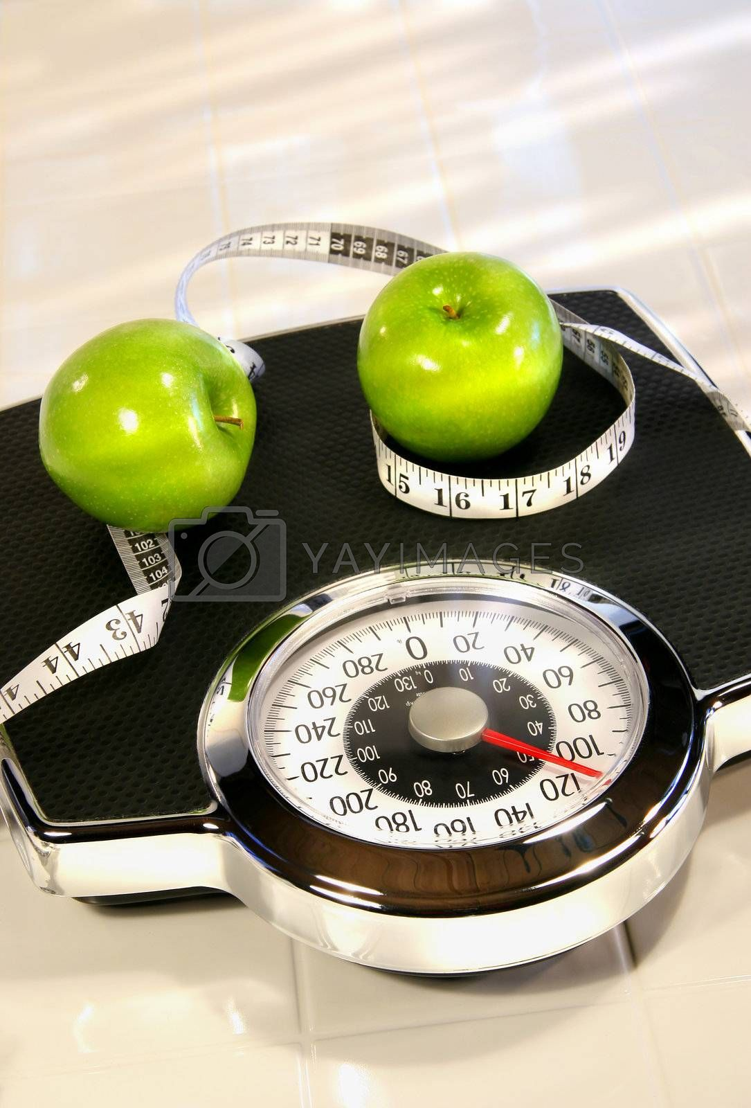 Weight scale with green apples on white tile floor