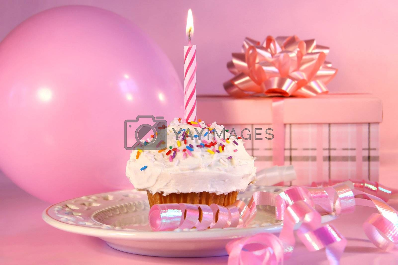 Little cupcake with candle, ballon and gift on pink background