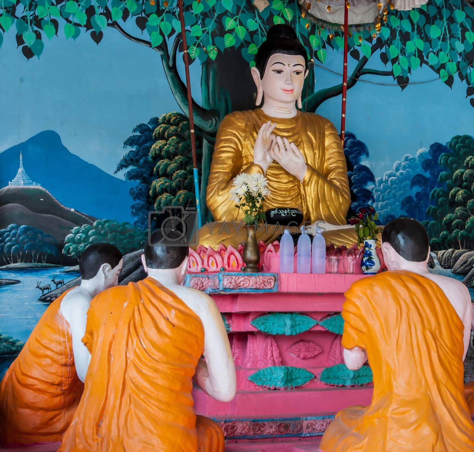 The statue of Buddha is giving a sermon to followers
