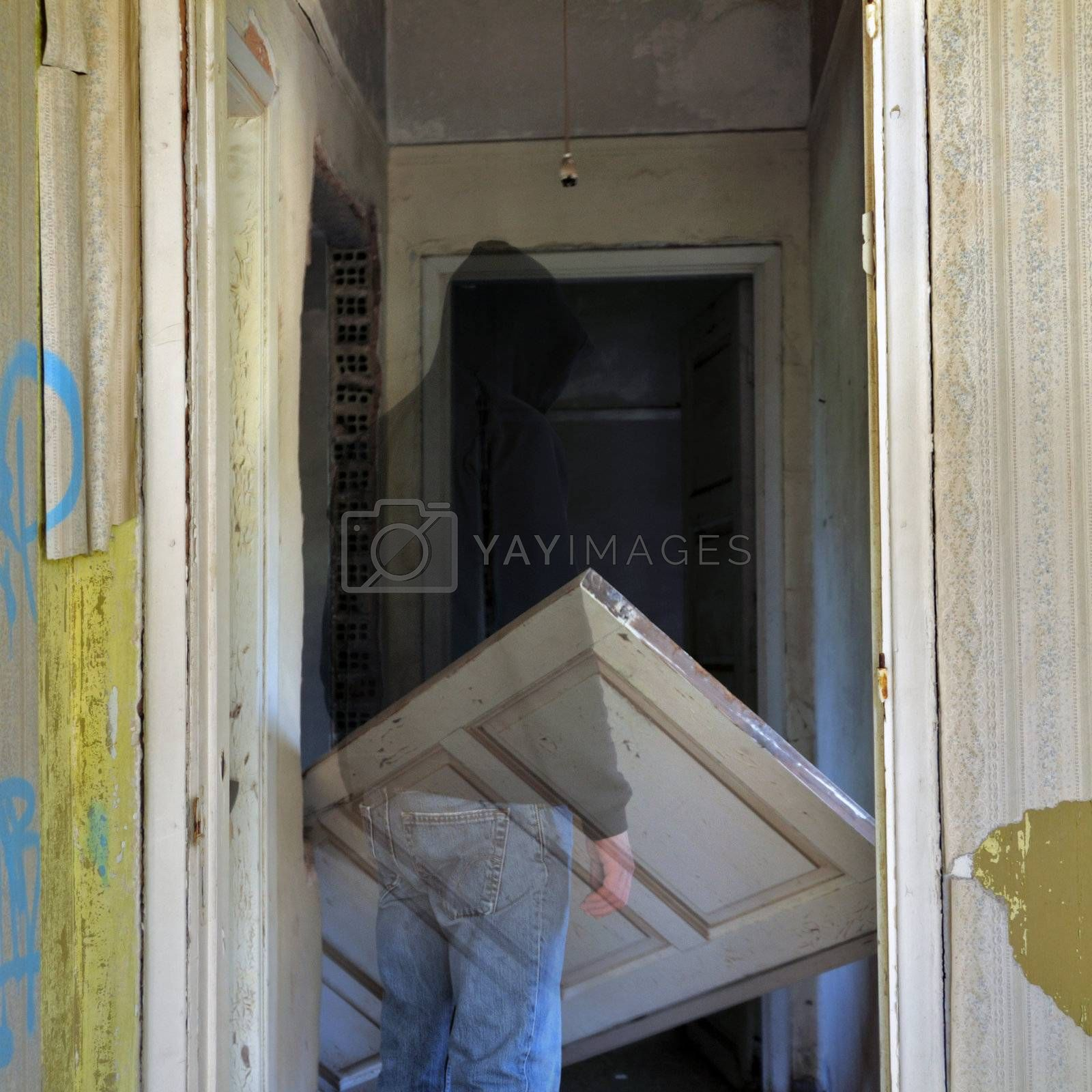 Ghost and unhinged door in the haunted hallway of an abandoned house.