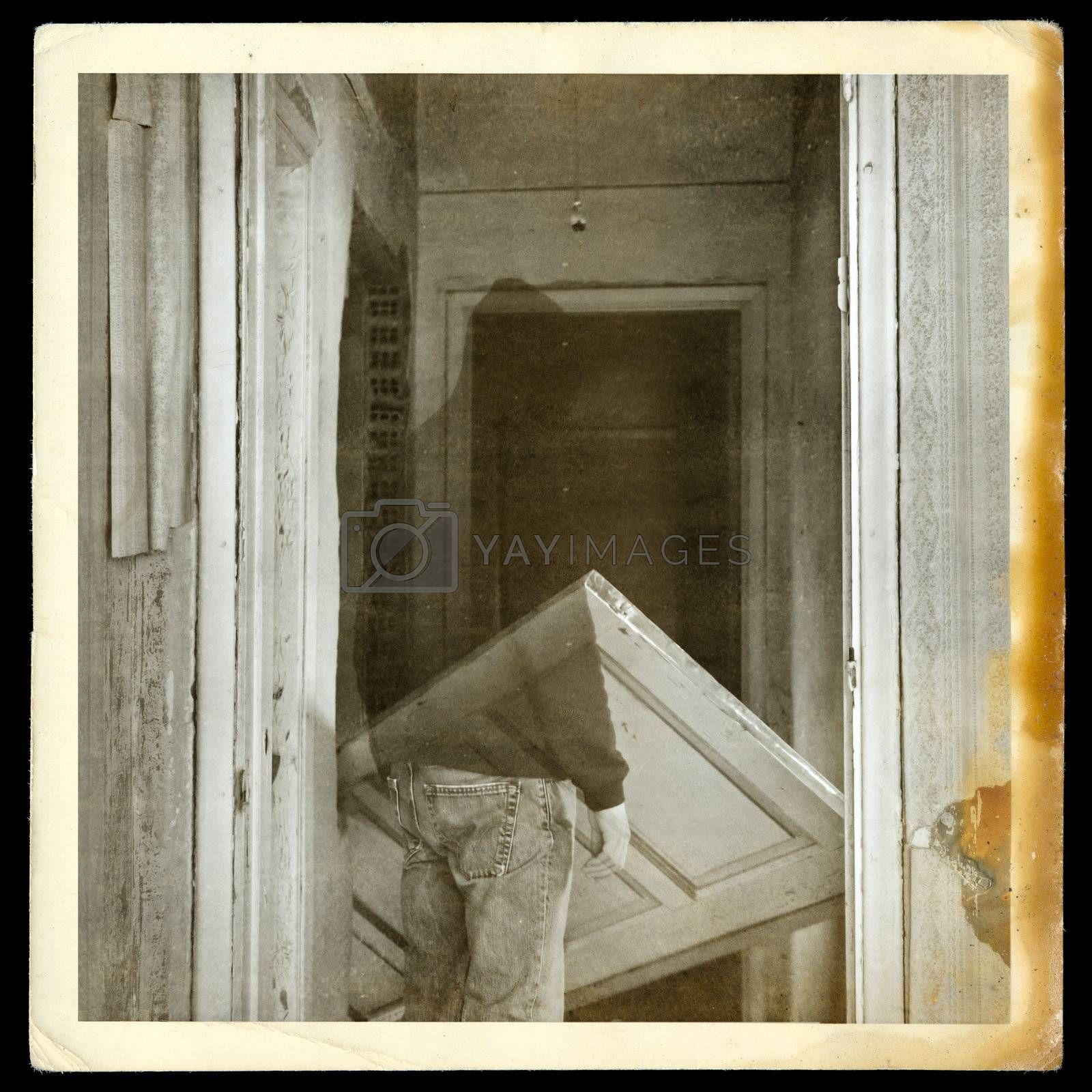 Vintage burned photograph of ghost in haunted hallways of an abandoned house.