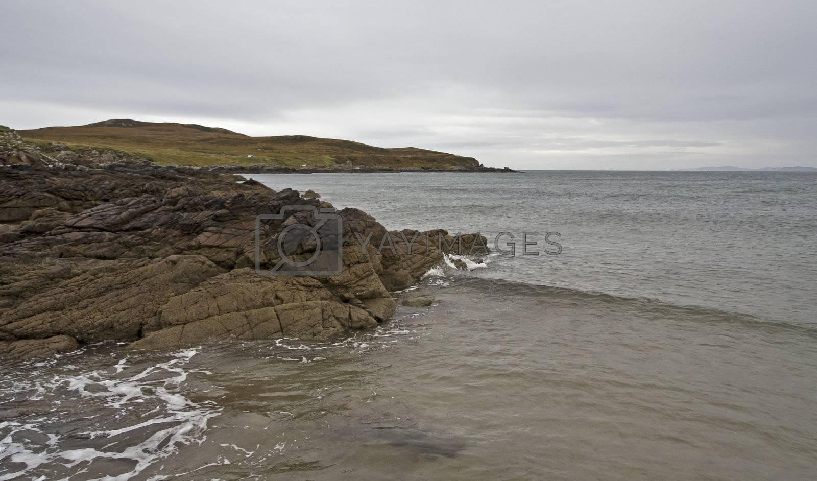 stoney coastline in scotland with small hill in background