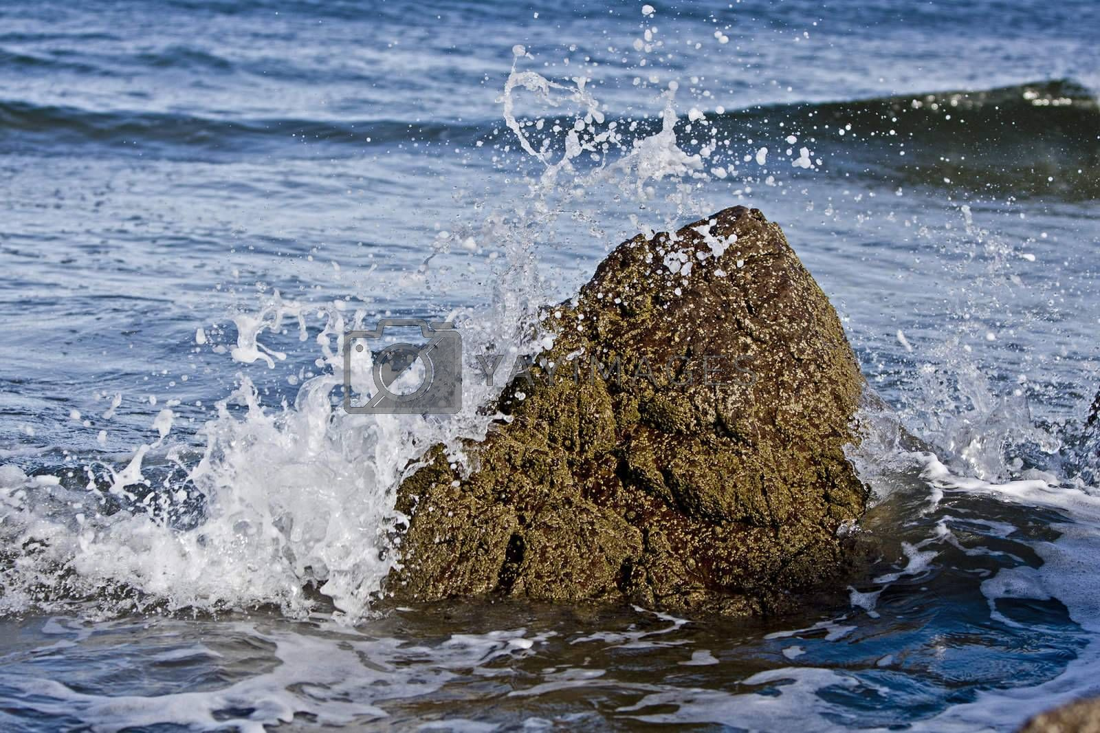small rock resisting the wave of the atlantic ocean. Scotland, UK