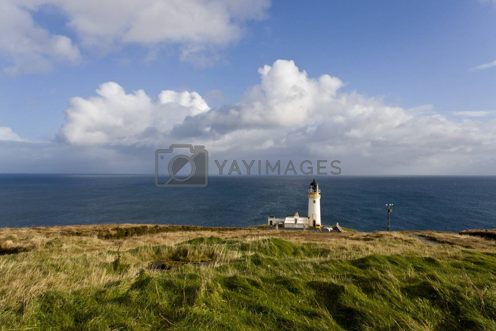 lighthouse at scotlands coast with cloudy sky in background