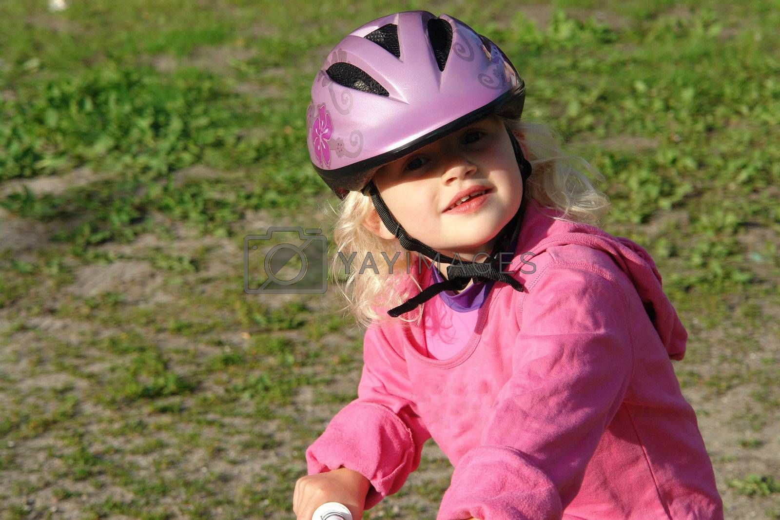 Cute little girl with a helmet riding a bike