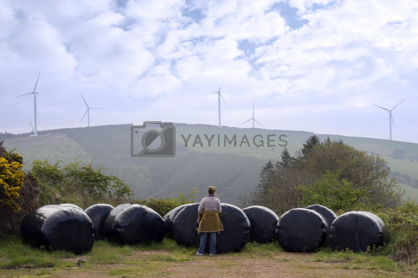 woman checking plastic wrapped bales with background windmills on lush irish countryside landscape in glenough county tipperary ireland