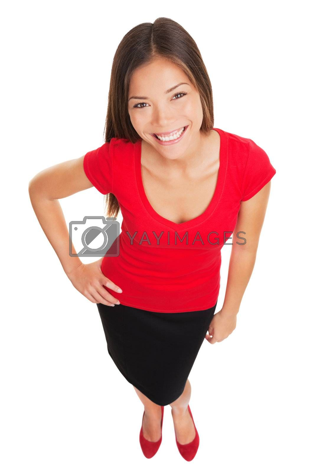 Beautiful stylish woman with charm smiling up at the camera with a lovely broad smile as she poses with her hand on her hip in a full body high angle portrait isolated on white. Asian Caucasian girl.