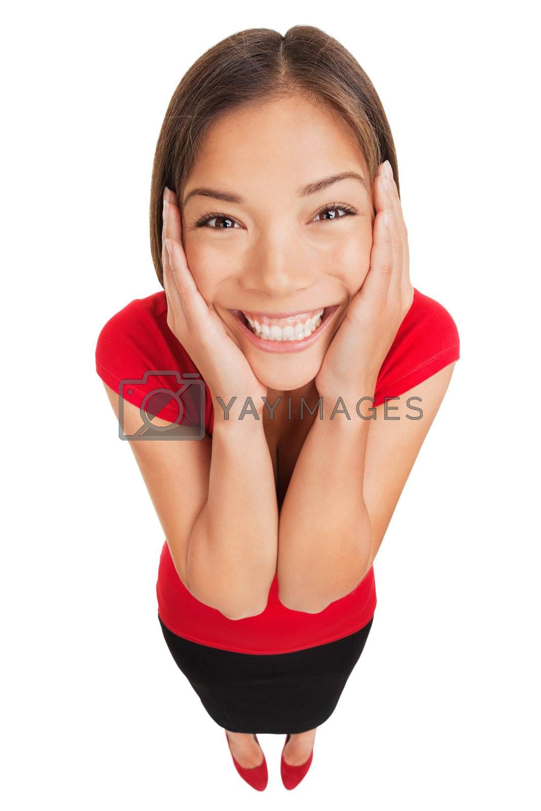 Happy woman overcome with joy holding her hands to her cheeks as she looks up at the camera lens with a beautiful smile, high angle full length studio portrait on white background. Multicultural model