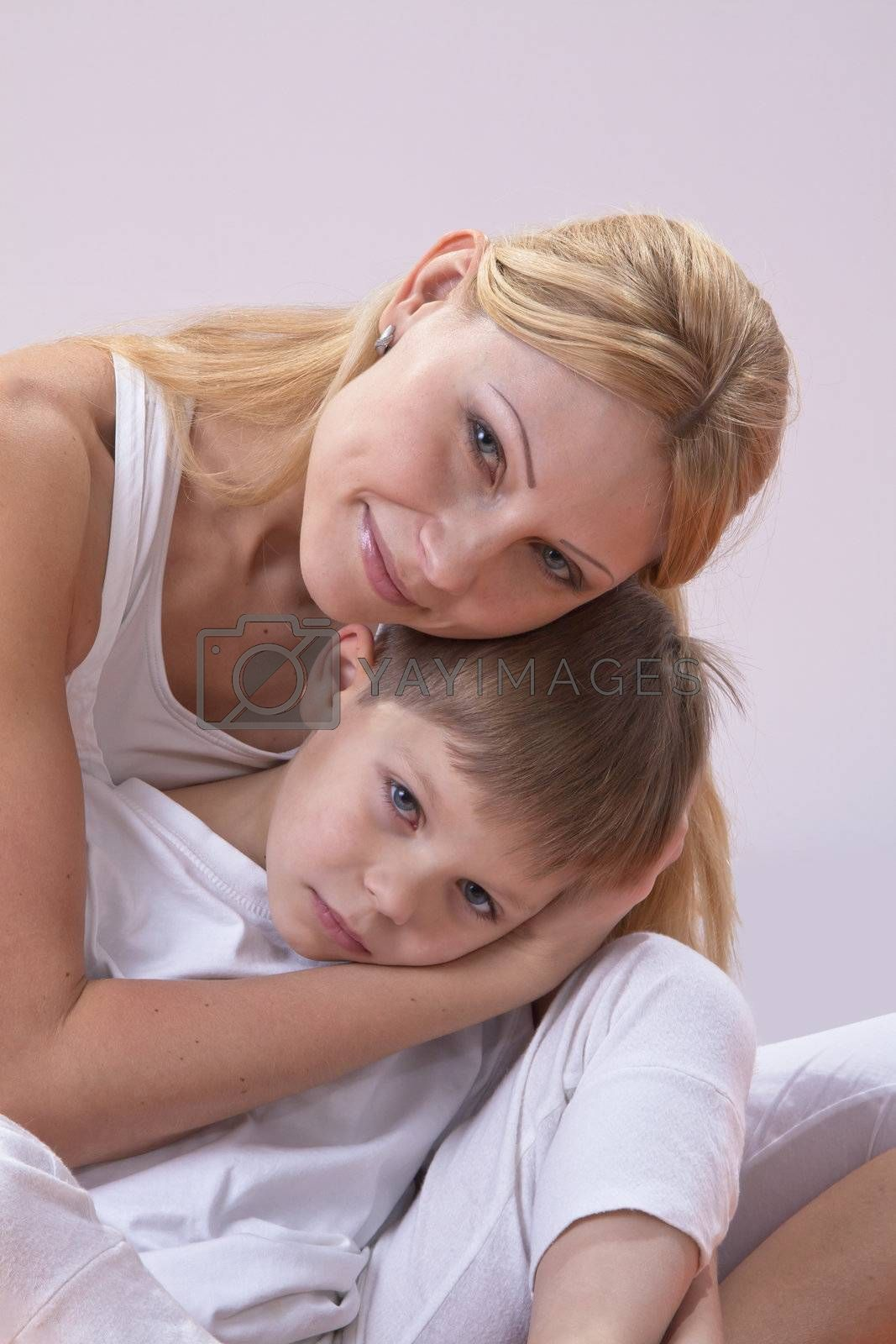 A beautiful young mother with her son rest during exercise yoga