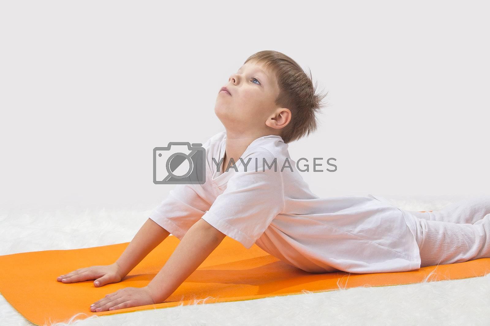 Children's yoga. The little boy does exercise.
