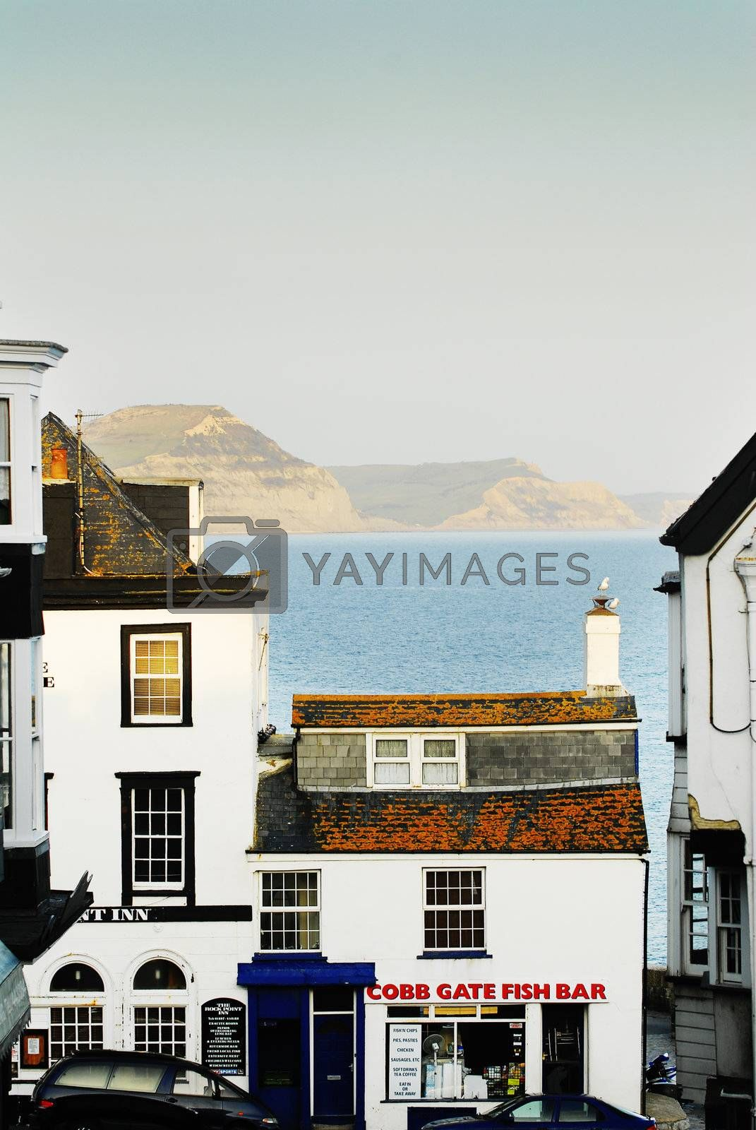 looking down to fish and chip shop takeaway lyme regis uk with sea and charmouth cliffs in background