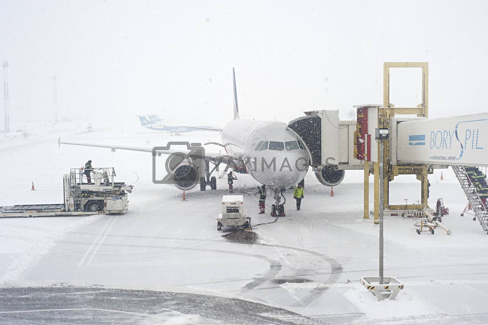 Kiev, Ukraine - January 12, 2013: Unidentified workers prepairing an airplane duirng the snowfall. Kiev was covered by around 20 inches of snow, the largest amount to fall in one weekend since records in 1889