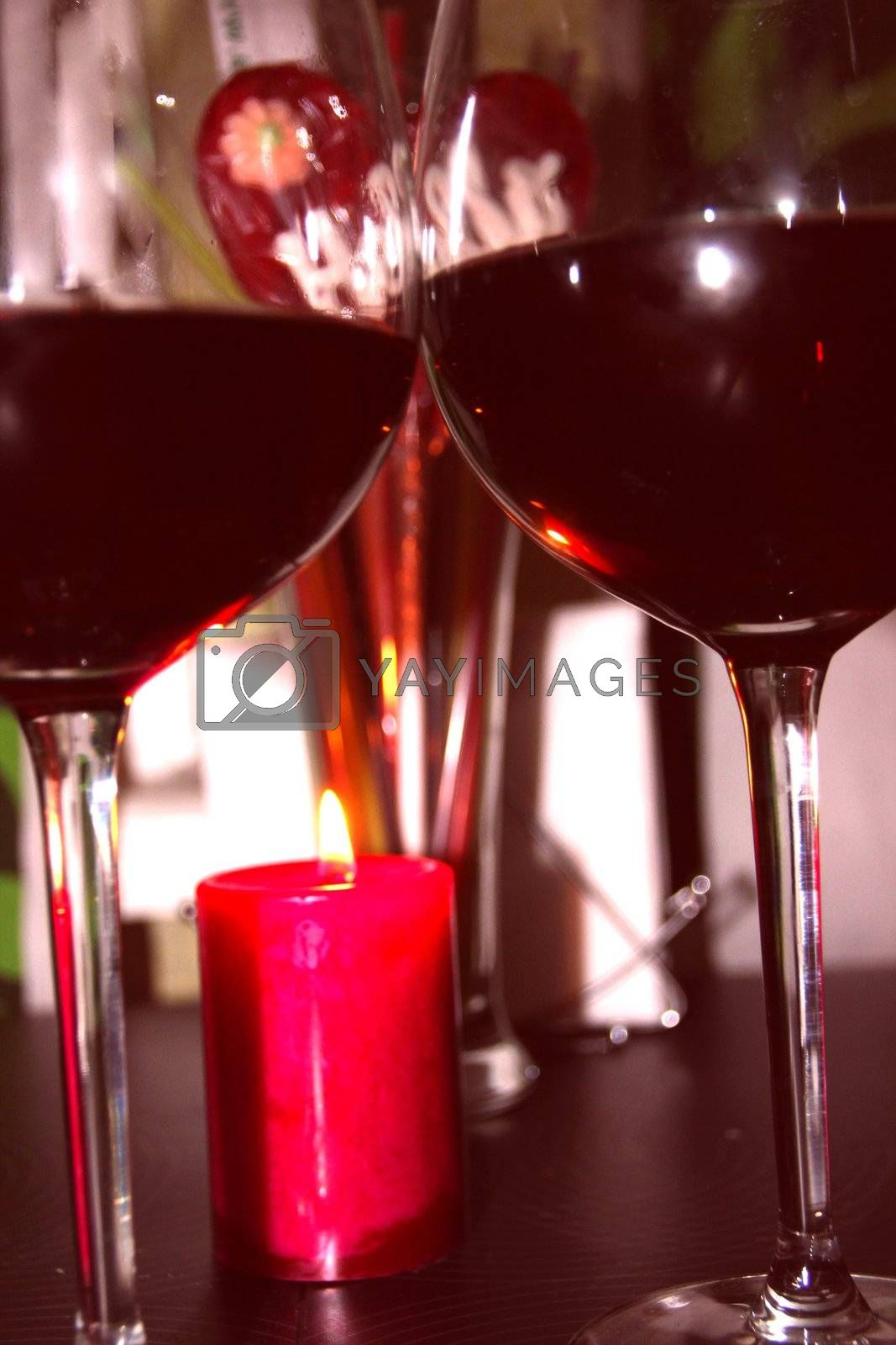 Two glasses of red wine next to the candles and candy in the form of the heart in the background