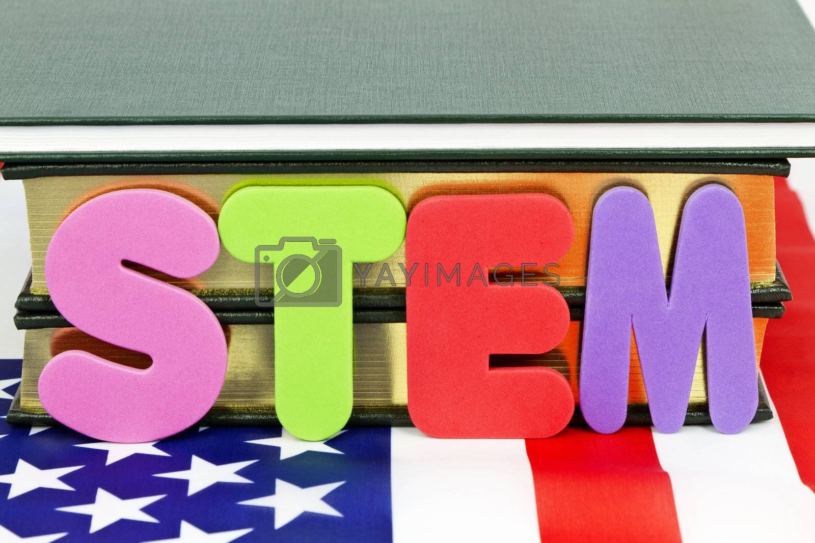 Popular designation of STEM education (Science, Technology, Engineering, and Mathematics) references life and career-ready skills for 21st century success. Letters S,T, E, M, placed before books and on American flag.