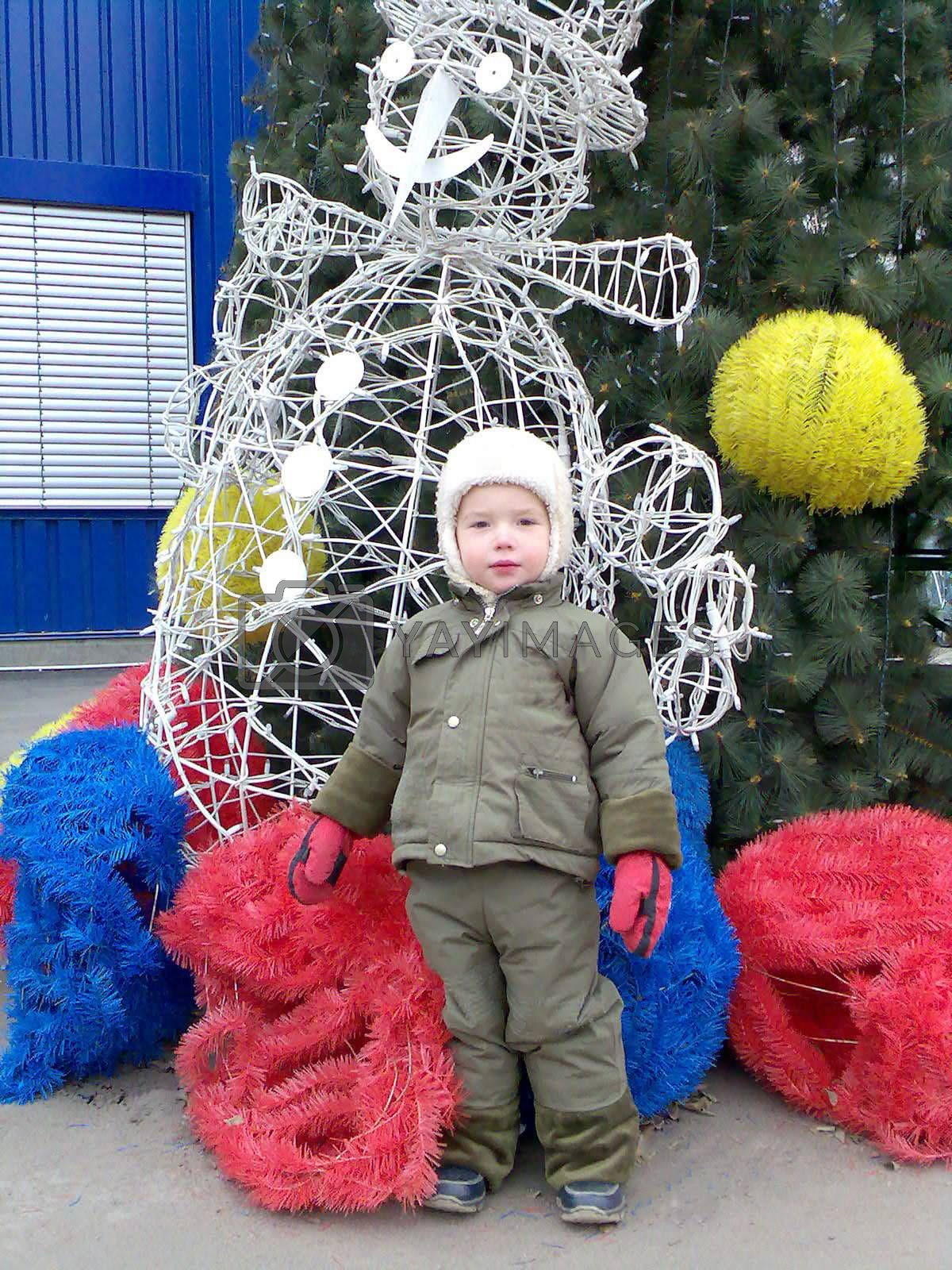 The kid next to the Christmas Tree