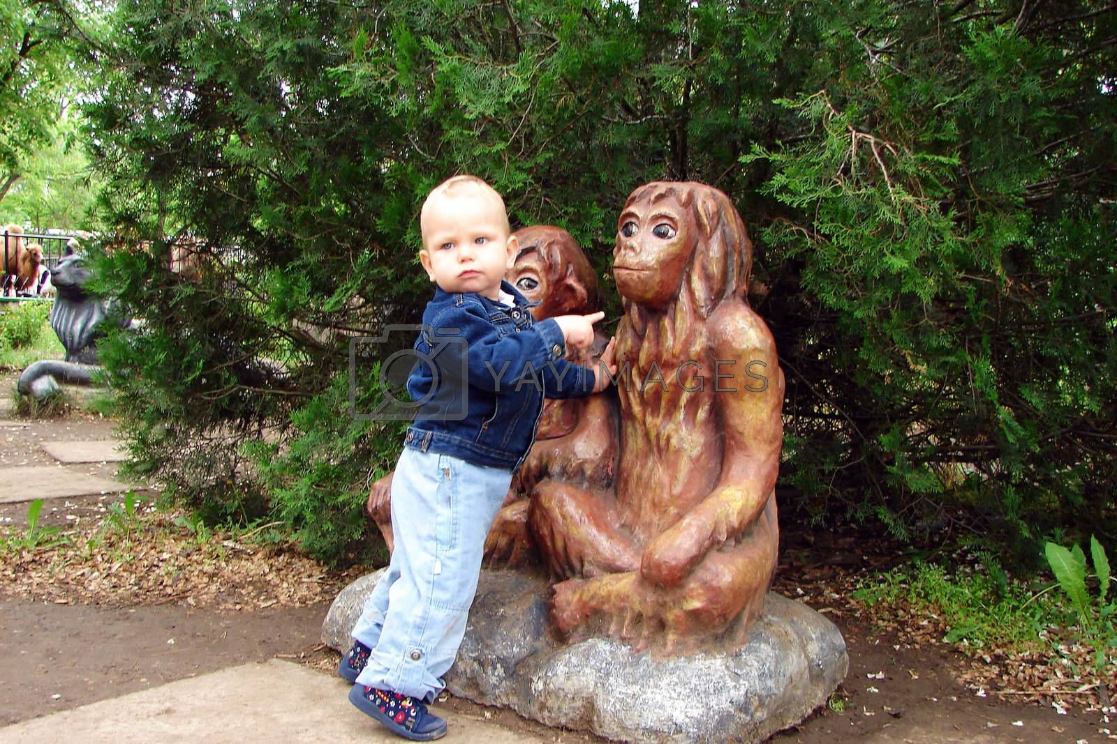 Babe in the city park next to the statues of monkeys