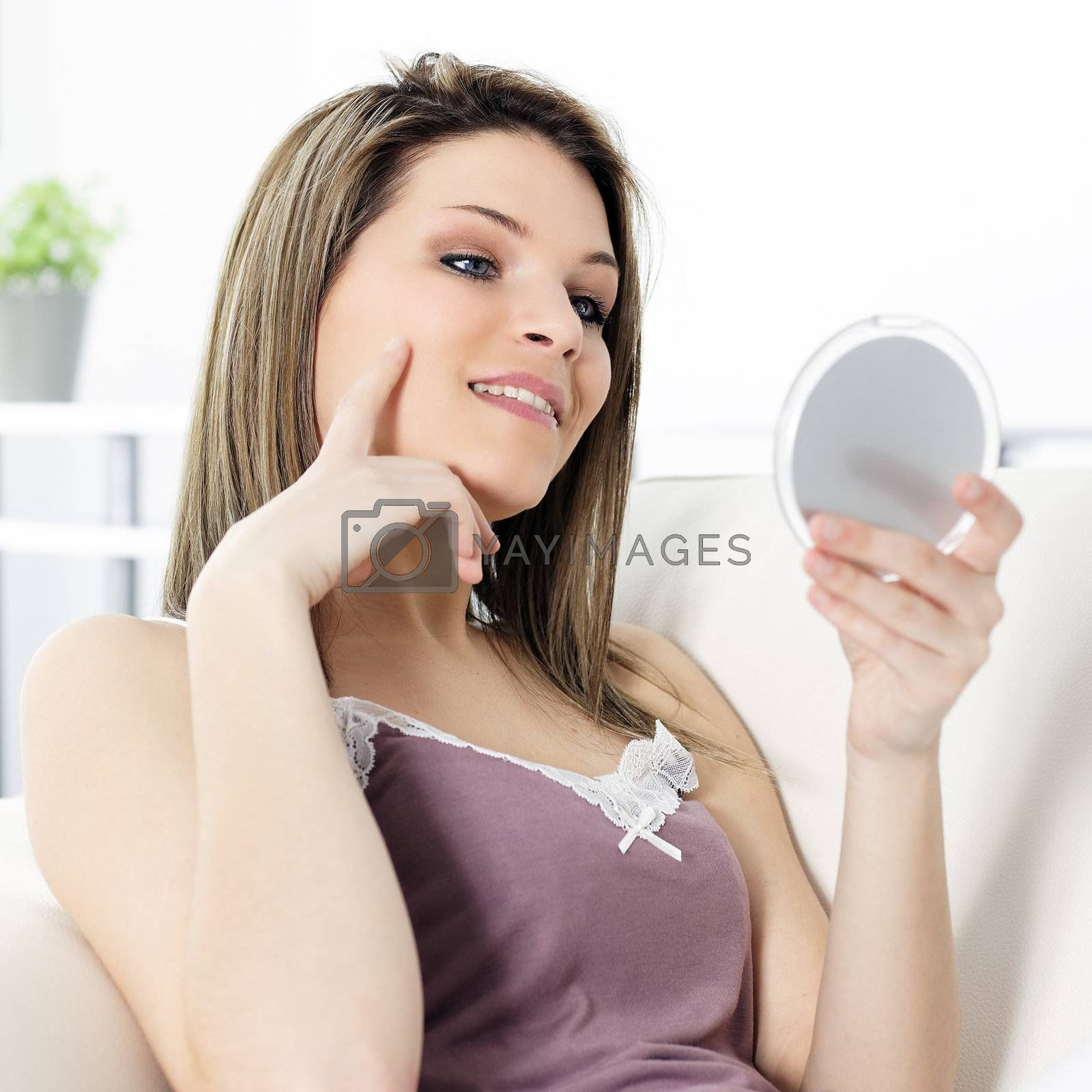 young beautiful woman looking his face in a miror