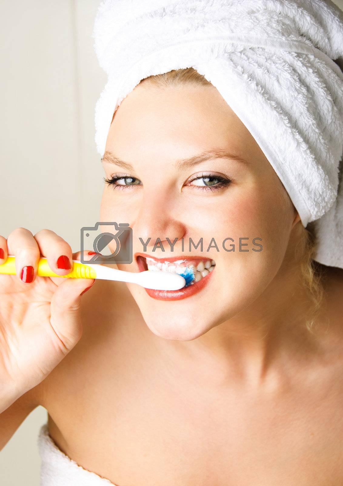 happy young beautiful woman brushing her teeth in the bathroom