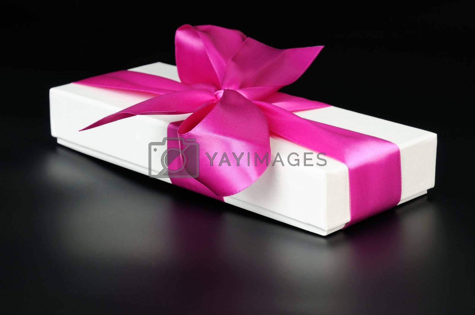 Gift box with a big pink bow. On a dark background.