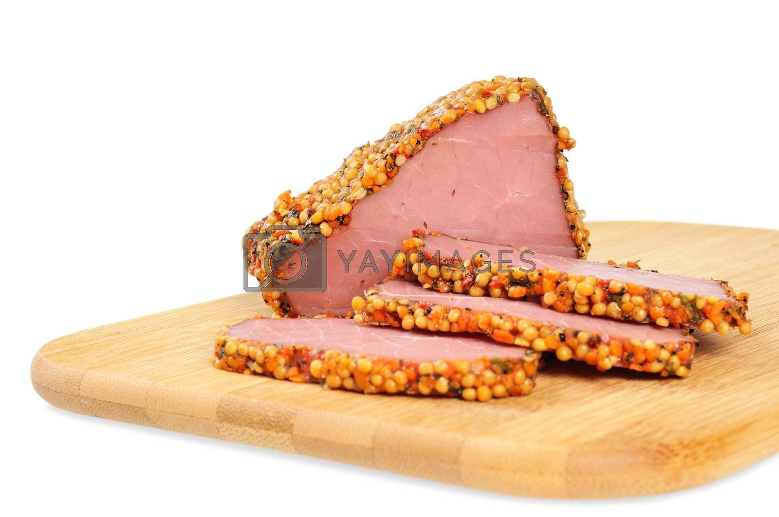 Piece of a ham with spices on a wooden board. Onwhite background.