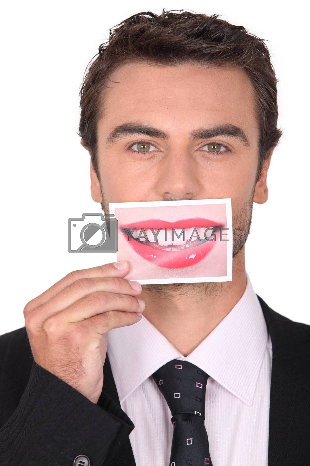 brown-haired young man holding picture of female mouth smiling Dubbroca_Joffrey_160410