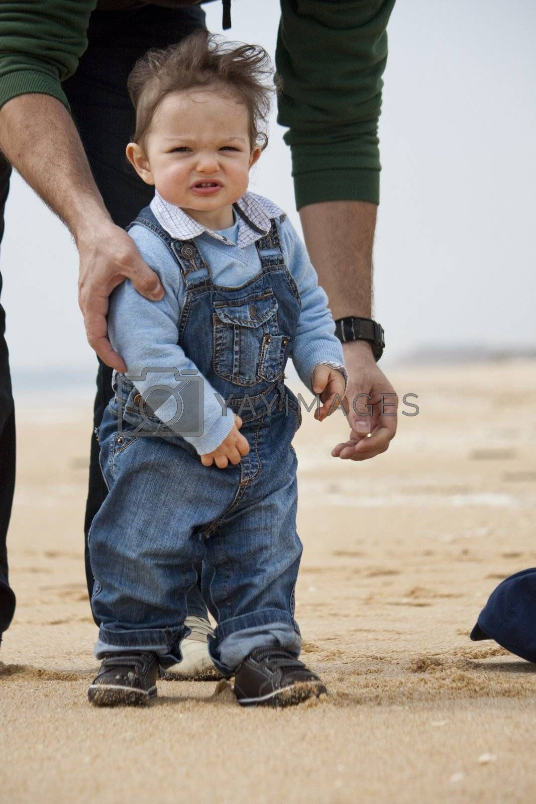 View of a happy young child walking on the beach.