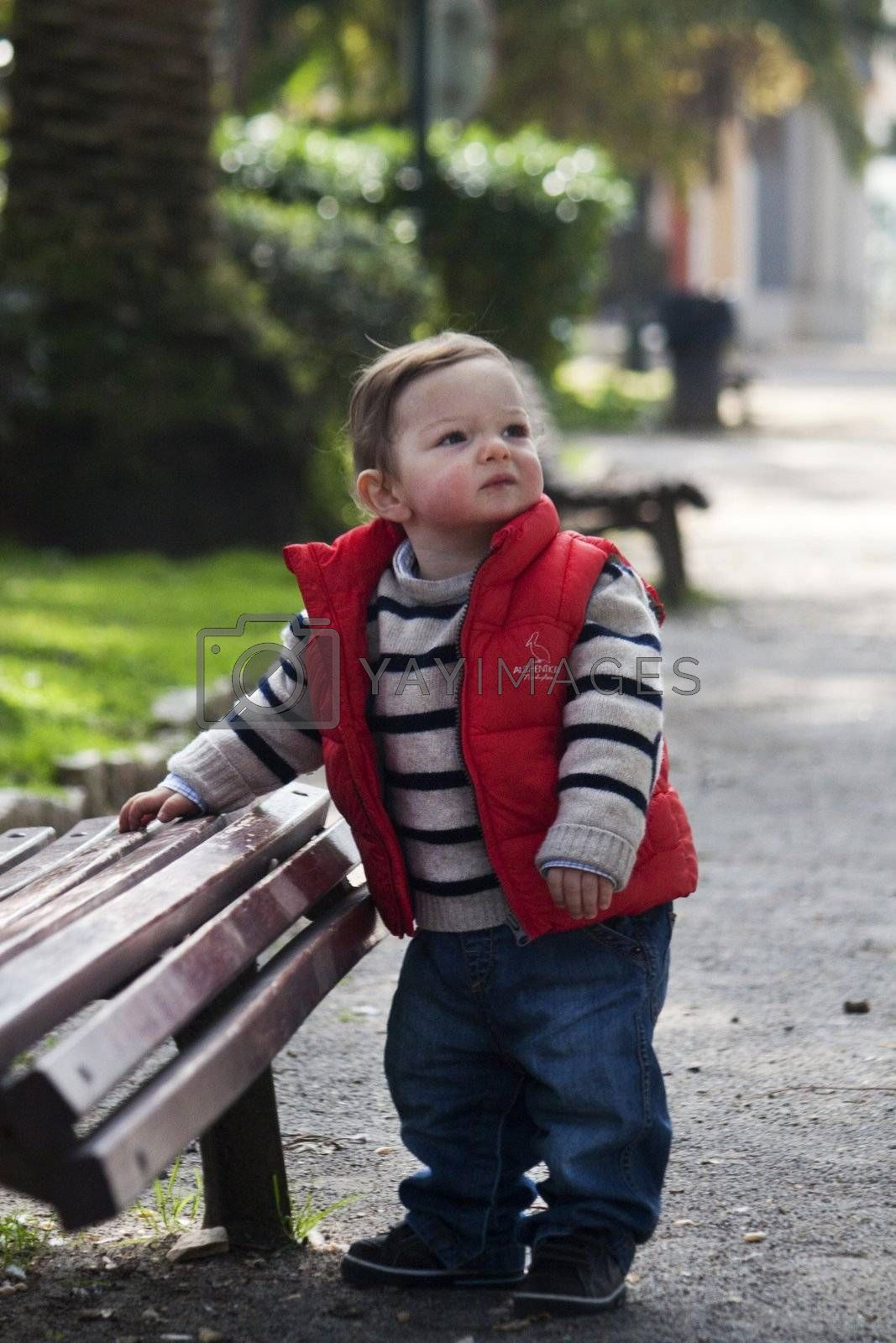View of a young child next to a bench on a urban park.