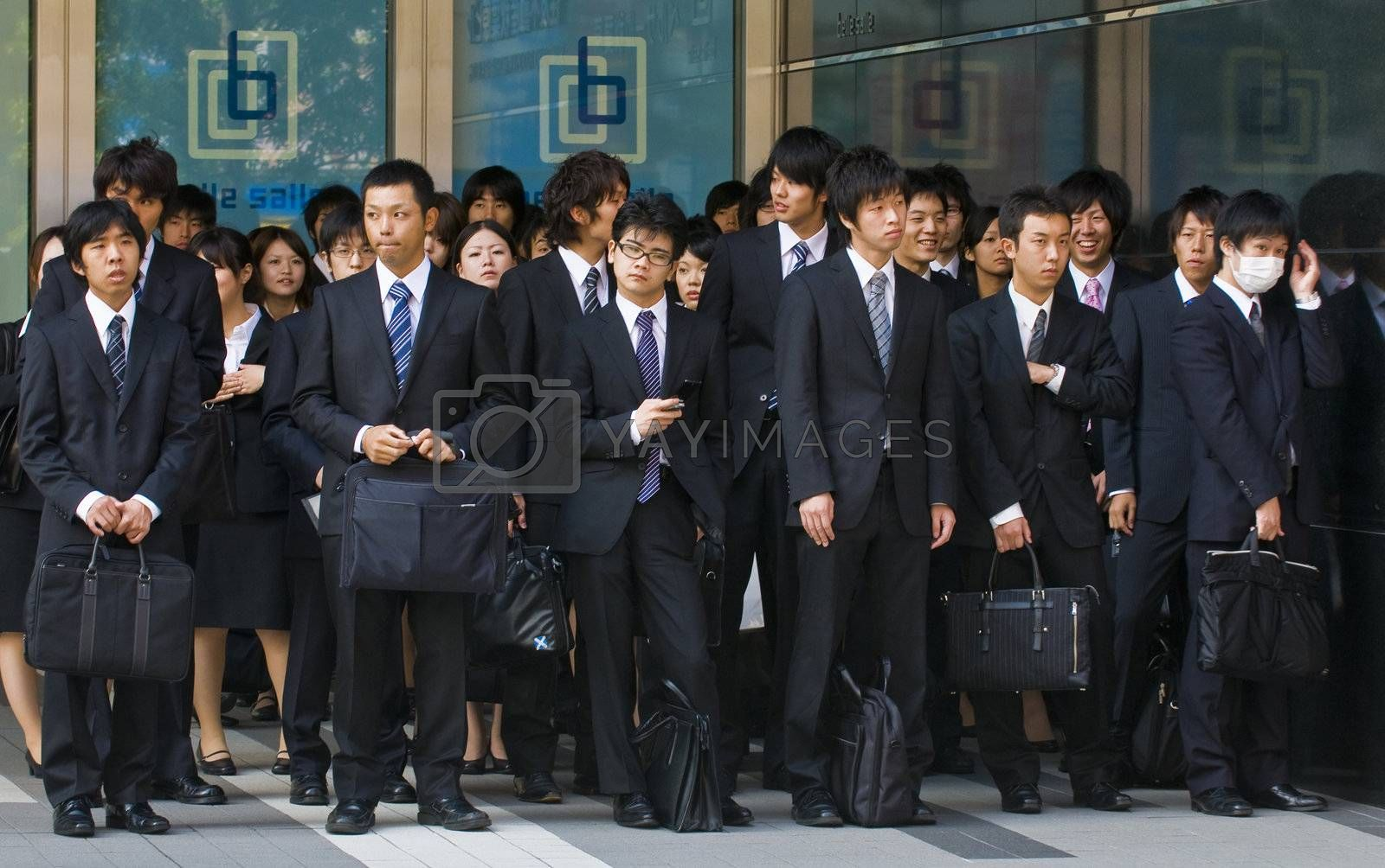 TOKYO - OCT 29 : Japanese office workers stands outside an office building in Tokyo Japan financial district on October 29 2009