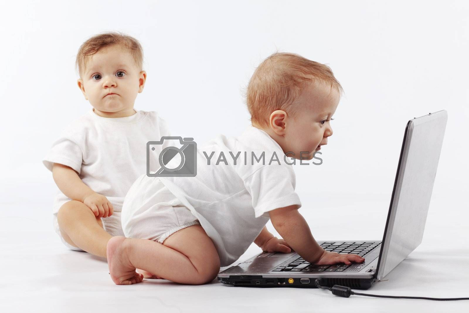 Two cute babies playing with laptop