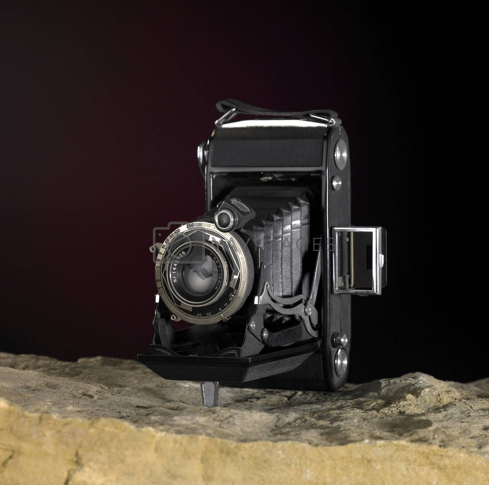 Still life with nostalgic camera on stone ground in front of dark back