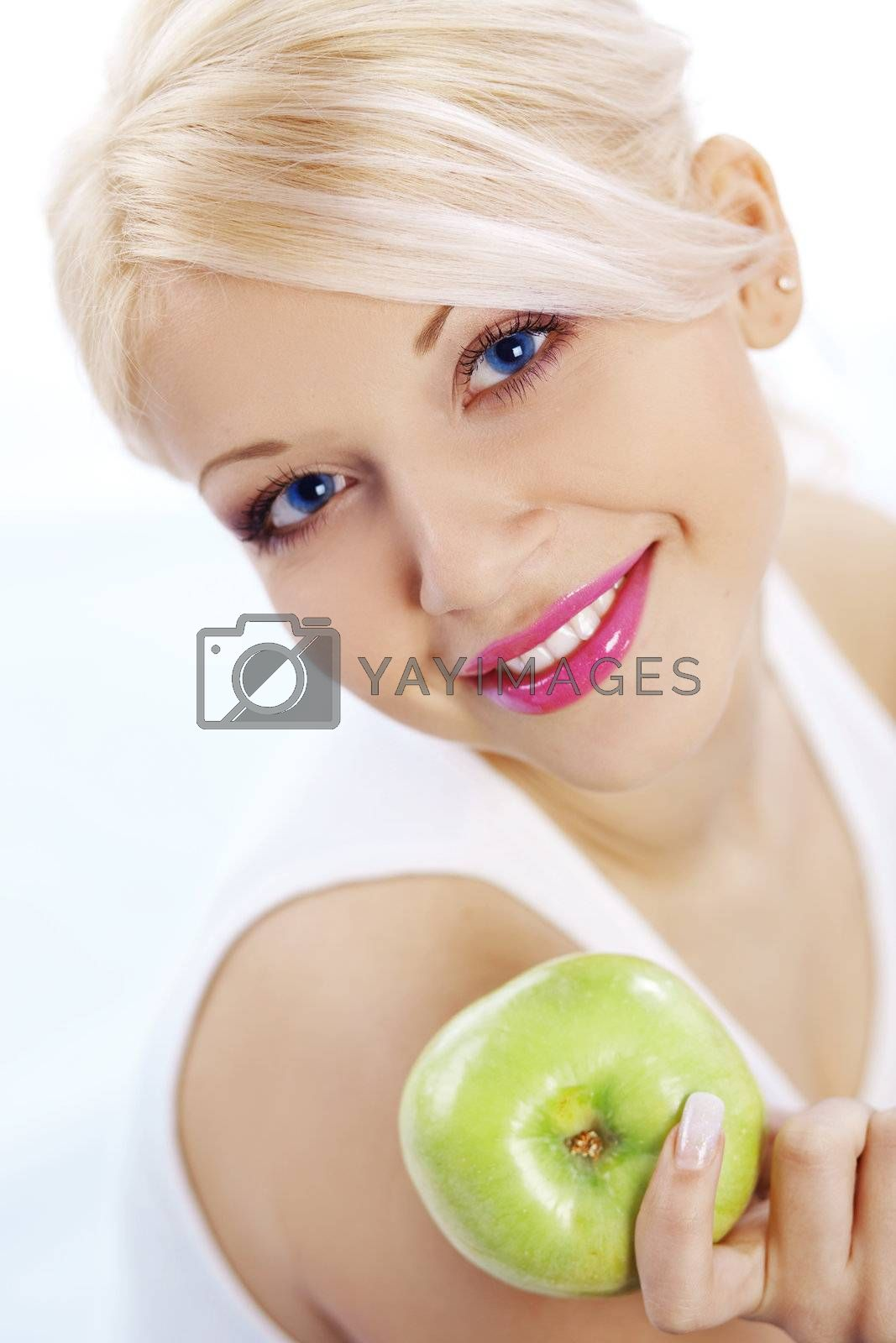 Bright spring portrait of happy healthy woman holding apple